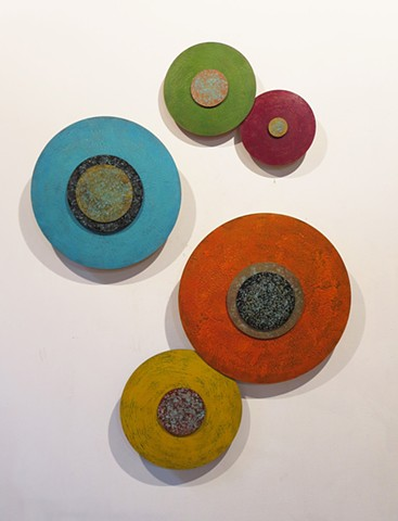 Abstract art installation wall sculpture of abstract disks painted with encaustic to create dimensional wall sculptural