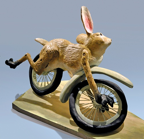 rabbit on wheels, mid-wipe out, struggles to hold on.