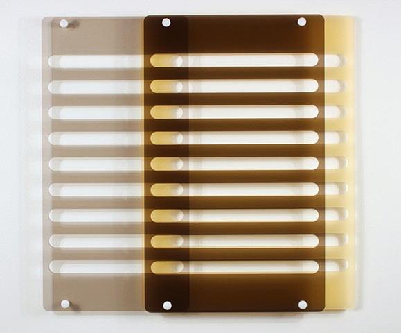 Geometric brown and yellow laser-cut acrylic sheet with spacers.