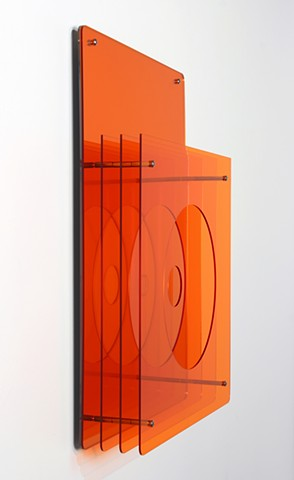 Geometric abstraction, based on number sequence, in mirrored and orange laser-cut acrylic.