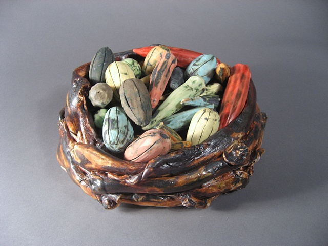 Pods are slipcast and twigs basket it porcelain. Underglazes and oxides are used for color.