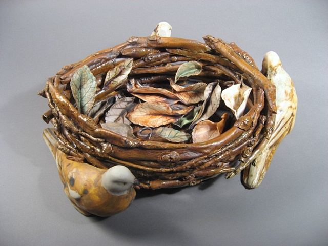 Slip cast birds surrounds twig basket. Leaves are loose in the basket. Judith Rosenthal