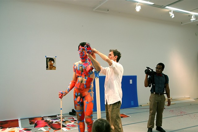 A male participant's body is photographed in a pose of his choosing in advance of the performance. During the performance the printed images are applied directly onto the corresponding parts of the performers body.