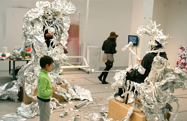 Two teenagers started out making aluminum foil mask to conceal themselves. Visitors were invited to further adorn the participant with aluminum foil (adding not subtracting).