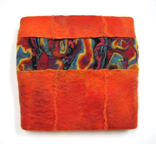 A handmade felt wall piece made of dyed, unspun wool and  yarns, by Sharron Parker.  Abstract, colorful, modular.