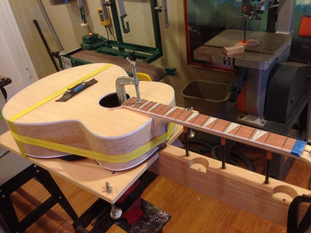 Guitar is set up on neck jig, in floor vise, using band clamp to draw dovetail tight.