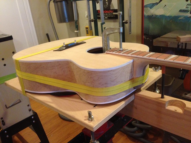 Close-up of band clamp in use, gluing neck heel dovetail joint.
