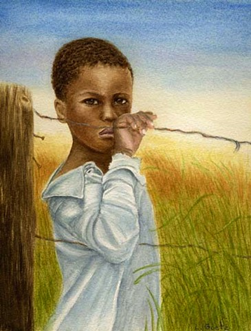 Young african boy standing at the fence.