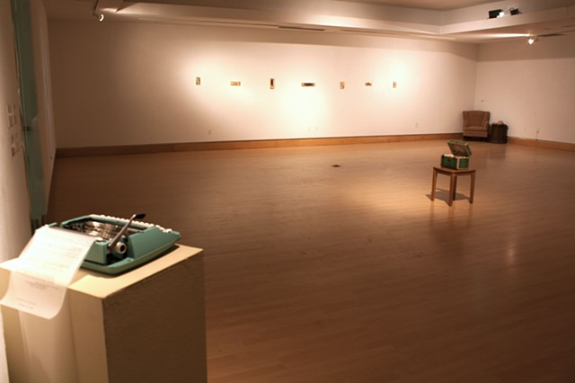 """Gallery shot of typewriter for viewer  commentary (closest) and three works:  """"Is this when the grass gets greener?"""" (middle) """"Nondescript"""" series (back left) """"Please, hold"""" (back right)"""