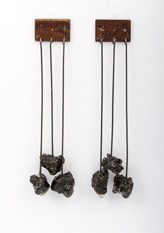 a pair of earrings made of rusted steel, sterling silver, steel wire, asphalt and resin.