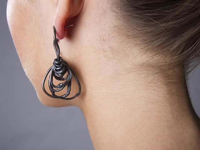 an asymmetrical pair or earrings composed of welded steel wire chain links and sterling silver.