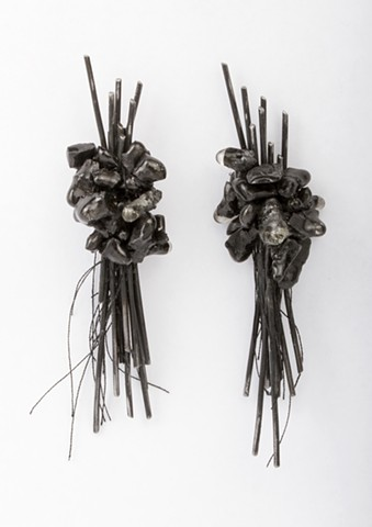 a one-of-a-kind pair of asymmetrical earrings composed of welded steel clusters of wire, sterling silver and handmade crushed graphite beads covered in resin and attached with black thread