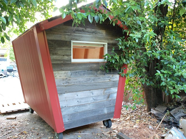 Reclaimed redwood fencing and red corrugated metal siding.