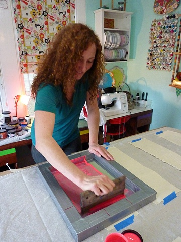 Maggie printing her band's logo on cloth for patches