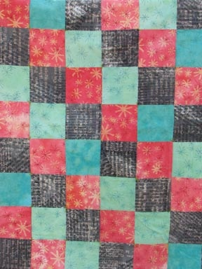 quilt, machine pieced and hand tied.  hand-dyed, silkscreened, discharged cottons.