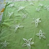 flowers cut from freezer paper, waiting to be ironed onto dyed cotton and rolled over with thickened dye...