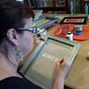 Kat painting a screen