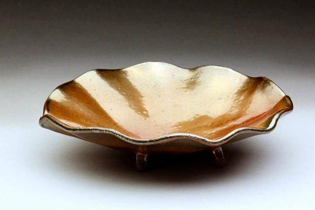a wavy edged bowl with small feet