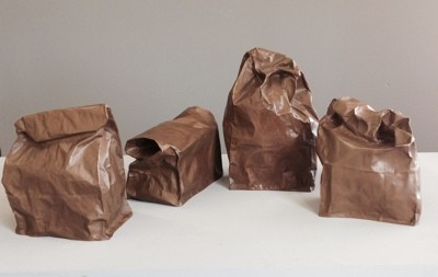 a realistic trompe l'oeil of paper lunch bags,in bronze, having a conversation. by Laura Evans