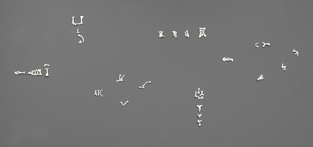 bonelike sculptures arranged as cryptic pictograms or runes by Laura Evans