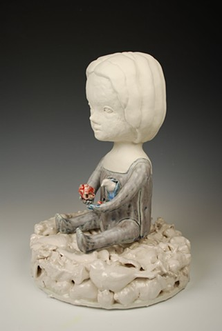 Coiled porcelain doll figure seated on a base of cast porcelain objects. A bird is emerging from her body.
