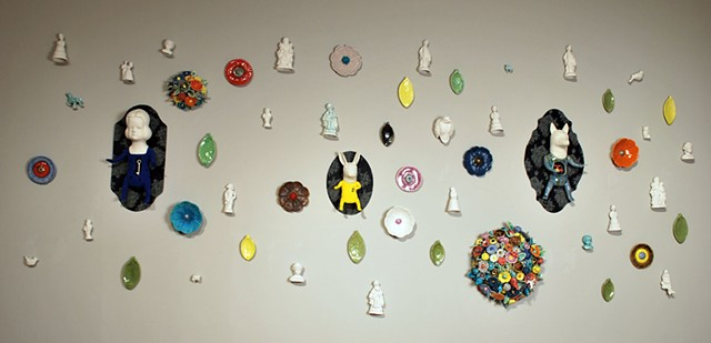 Wall installation with porcelain wall figures, flocking, cast flowers, leaves, and objects, and paper frames..