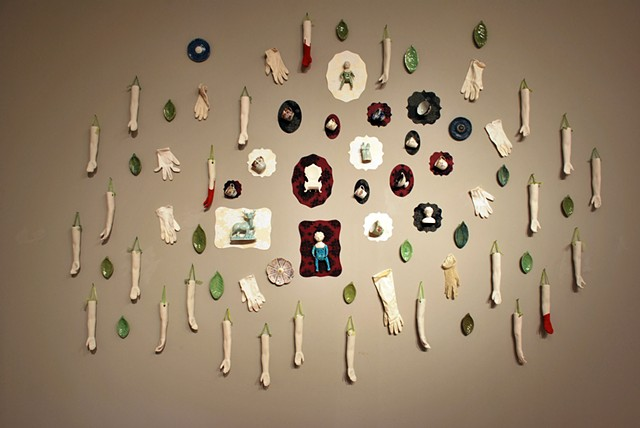 Wall installation with cast porcelain found objects, porcelain arms, flocking, ladies white gloves, doll figures, flowers and leaves