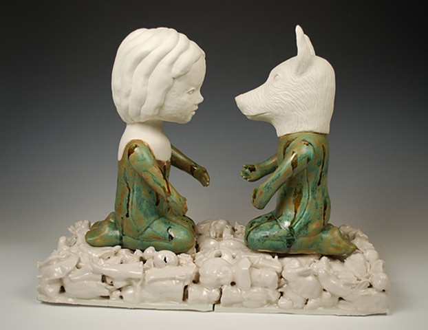 Two coiled porcelain figures sitting on a base made from slip cast porcelain objects.  One figure has a carved wolf head.  The figures reach out to each other.