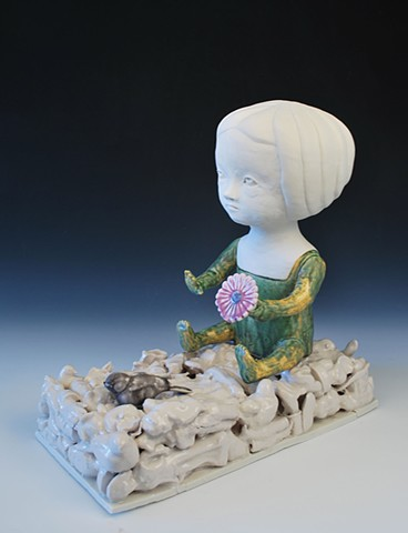 Coiled porcelain doll figure seated on a base of cast porcelain objects.  The figure holds a flower and looks out at a colored, cast bird.