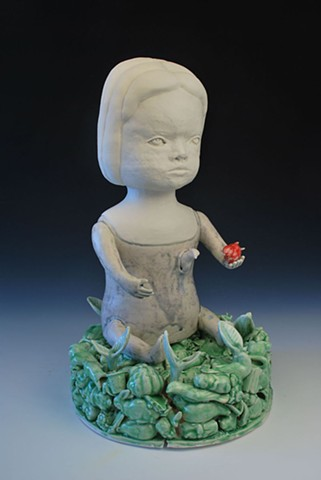 Coiled porcelain doll figure seated on a base of cast porcelain objects. She holds a red bird and one emerges from her body.
