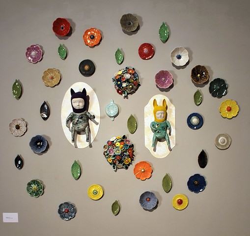 Wall installation with porcelain wall figures, flocking and cast flowers, leaves and objects.