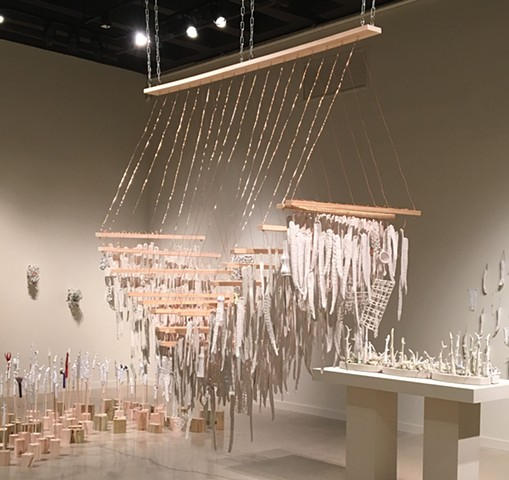 Suspended sculpture Installation with porcelain rods, cage forms and objects