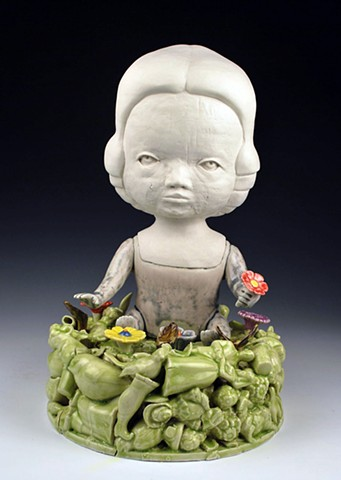 Coil built, porcelain doll figure seated on a base of cast porcelain objects and flowers.
