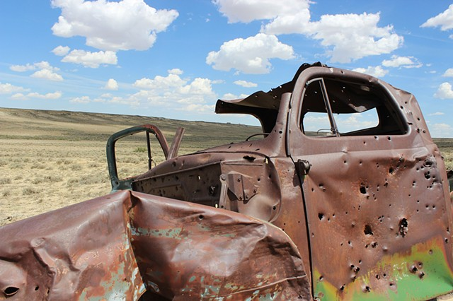 Abandoned truck shot full of holes, Red Desert Region, WY