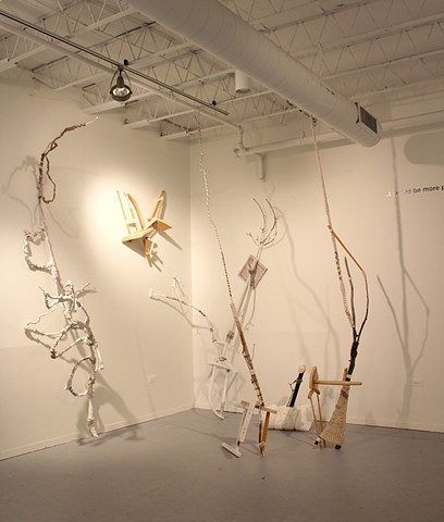 sculptural installation made of found furniture, tree limbs, jute, cotton yarn, gesso, paint, PVC