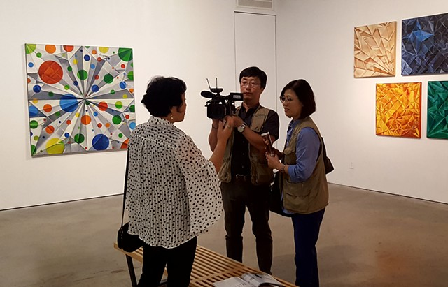 Artist Chun Hui Pak being interviewed.