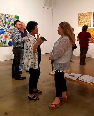 The artist talks about her art to a visitor.
