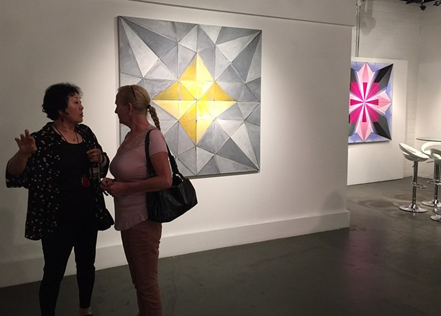 Artist Chun Hui Pak discusses her art with the first visitor to the opening