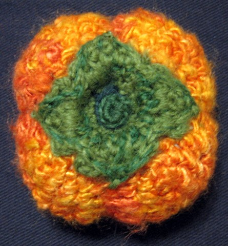 Crochet persimmon fruit toy yarn fiber art by Pat Ahern.