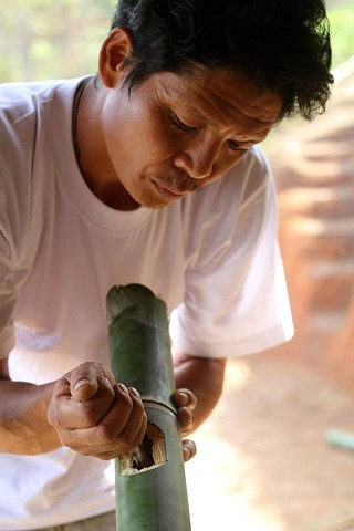 Karen man cooking rice in a bamboo pole