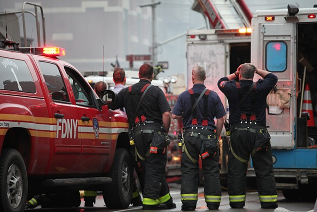 Fire fighters observe the scene of the Con Edison gas explosion and resulting fire in New York's East Village on March 26, 2015; the incident resulted in two deaths, nineteen injuries, and the complete eradication of three adjoining buildings.