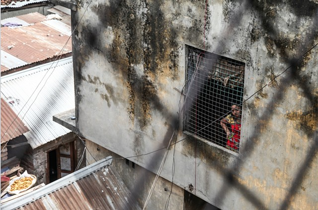 A young prostitute stares outside of a hallway window at the Rathkhola Brothel in Faridpur, Bangladesh.