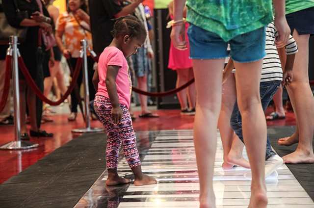 A young girl plays on F.A.O. Schwarz's iconic life-sized piano for the last time on July 15, 2015; the legendary Manhattan store will close this week after being in business for almost 30 years due to rising rental costs.