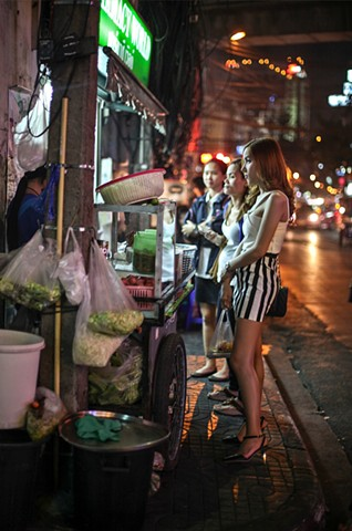 A group of sex workers stop by a roadside food cart in Bangkok, Thailand.