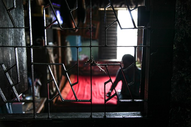 A sex worker, who shares her room with another prostitute, awaits her next customer quietly on her bed in the Rathkhola Brothel in Faridpur, Bangladesh.