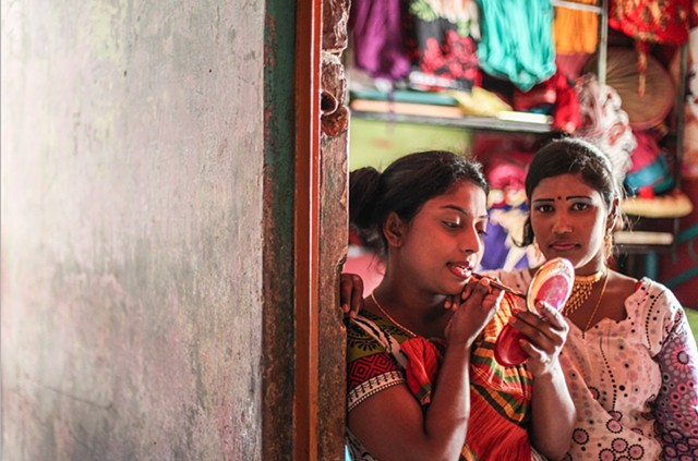 A sex worker in the Rathkhola Brothel in Faridpur, Bangladesh fixes her makeup as her friend looks on. Men selling makeup periodically walk through these brothels, allowing the young prostitutes to prepare for incoming customers.