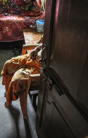 "A madam sits in the doorway of one of her workers' rooms at the Rathkhola Brothel in Faridpur, Bangladesh. ""Bonded"" prostitutes must pay their madam until the girls' original purchase price, paid by their former guardian, is paid back to the madam."