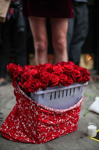 A bucket of red roses sits amongst candles and flowers at a rally in remembrance of the victims of the Orlando nightclub shootings at The Stonewall Inn in New York on June 12, 2016.