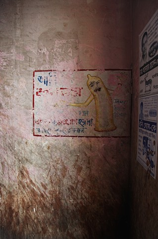 A worn sign advertises the benefits of condoms at the Rathkhola Brothel in Faridpur, Bangladesh. With an extremely high prevalence of STDs running rampant within the brothels, madams have begun educating their prostitutes about protecting themselves.