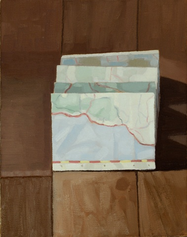 A still life painting of a folded map on a wood floor